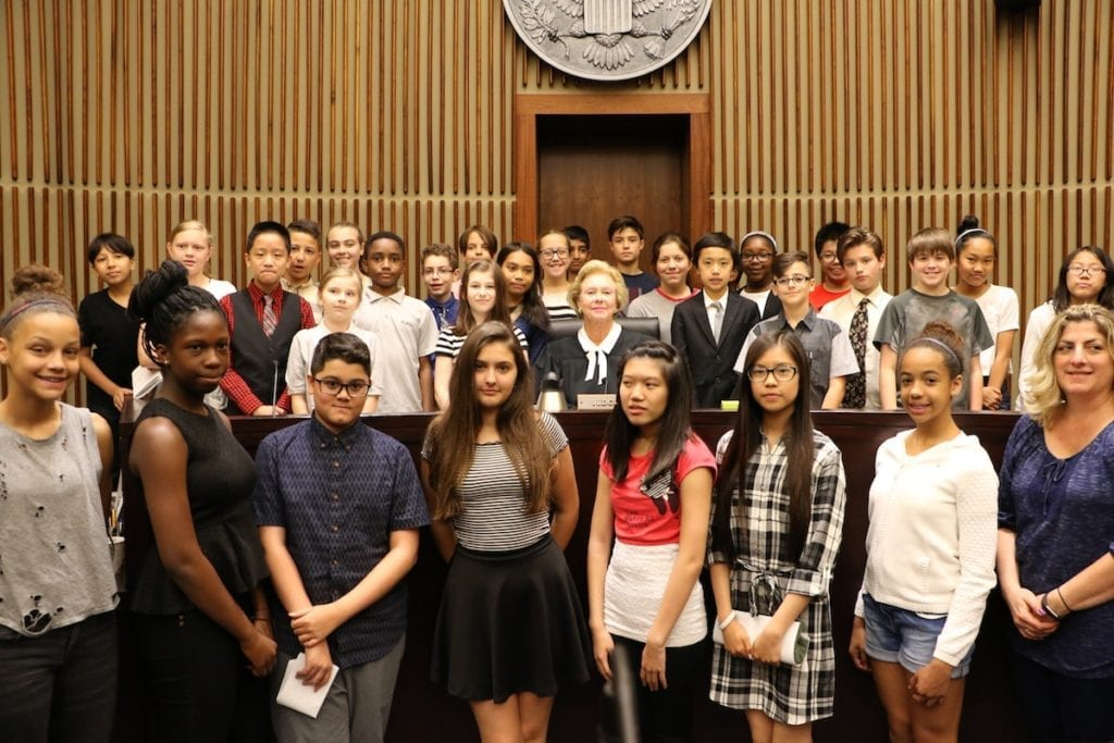 Judge Marjorie Rendell and local school students pose at the judge's bench in federal courtroom
